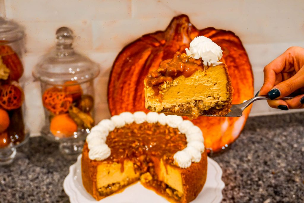 A slice of Pumpkin Pecan Cheesecake in focus with the whole cake in the background.