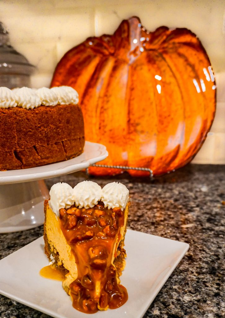 A slice of Pumpkin Pecan Cheesecake with pecan caramel oozing down the sides.