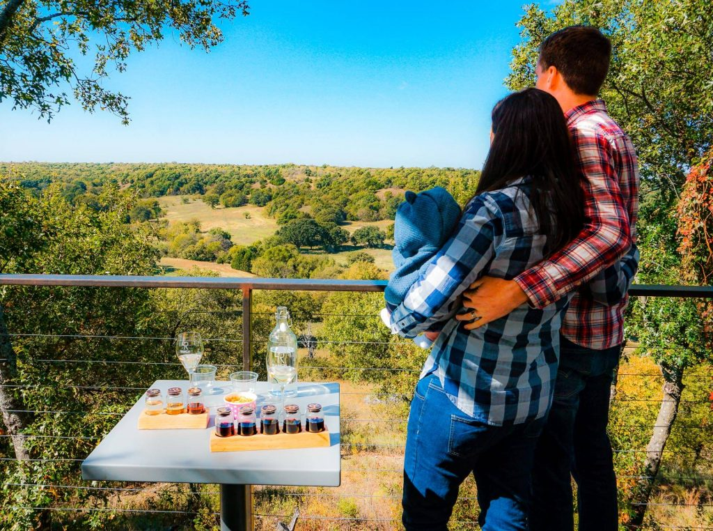 A couple with a baby looking out into the valley with a wine tasting at one of the best wineries in North Texas, 4R ranch Vineyards & Winery.