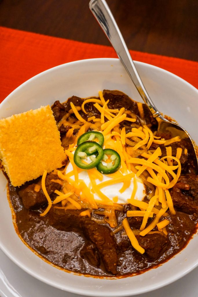 A bowl of authentic Texas Chili with a slice of cornbread, dollop of sour cream, sliced jalapeños, and shredded cheddar cheese.