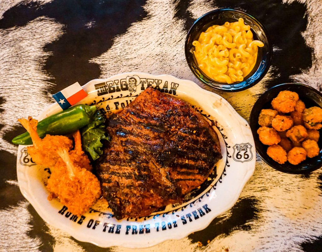 A plate of fried shrimp and an 18 oz steak with a side of mac n cheese and fried okra from The Big Texan Steak Ranch.