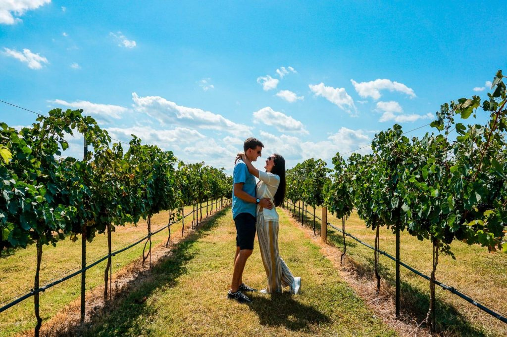 A couple in a wine vineyard in Fredericksburg, Texas - one of the best destinations on a Texas Hill Country road trip.