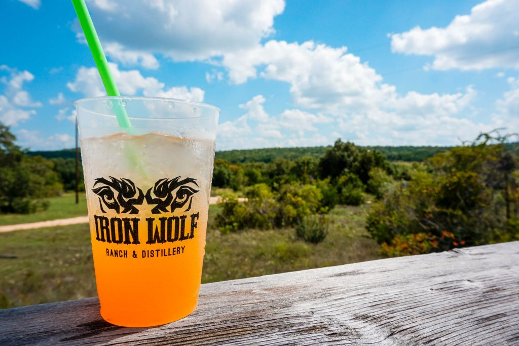 A mixed cocktail from Iron Wolf Ranch & Distillery with the Texas Hill Country in the backdrop.