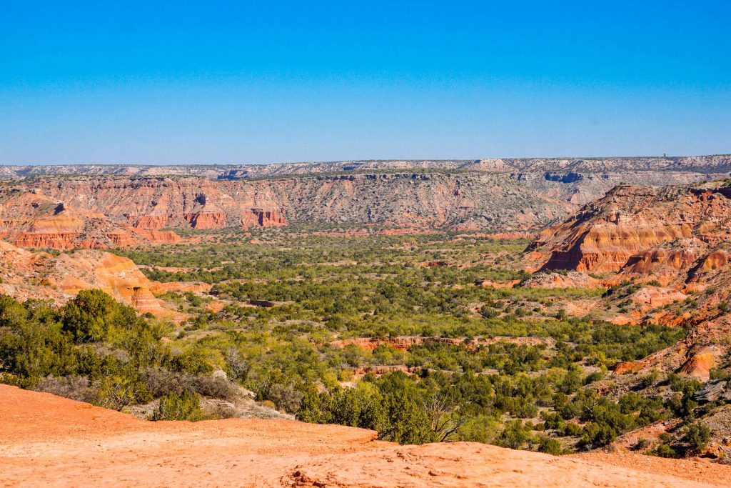 A valley of orange canyons with lush green vegetation from the Lighthouse at Palo Duro Canyon State Park.