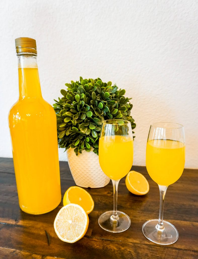 A bottle of homemade limoncello with two glasses full of limoncello and slices of lemons surrounding it.