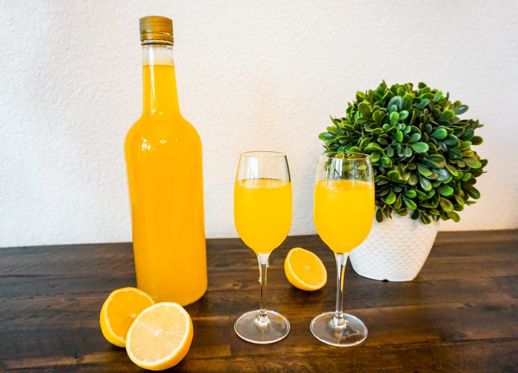 A bottle of homemade limoncello next to two glasses full of limoncello and sliced lemons around it.