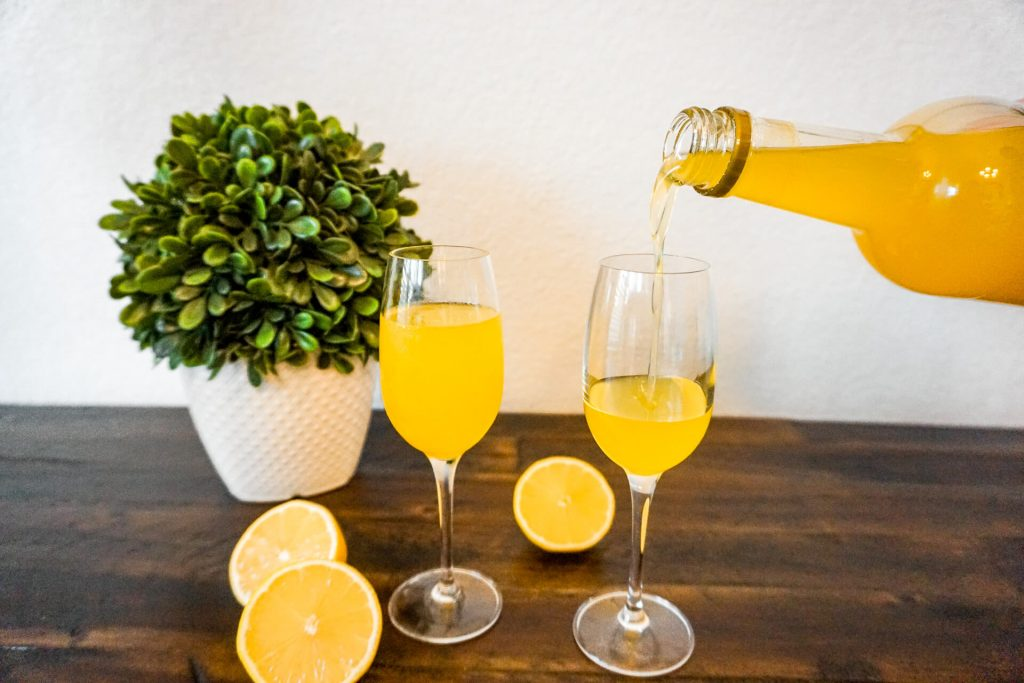 A glass of limoncello with a bottle of homemade limoncello being poured into a glass.