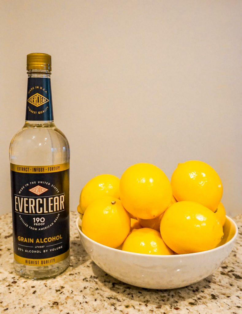 A bottle of Everclear and a bowl of Meyer lemons next to it.