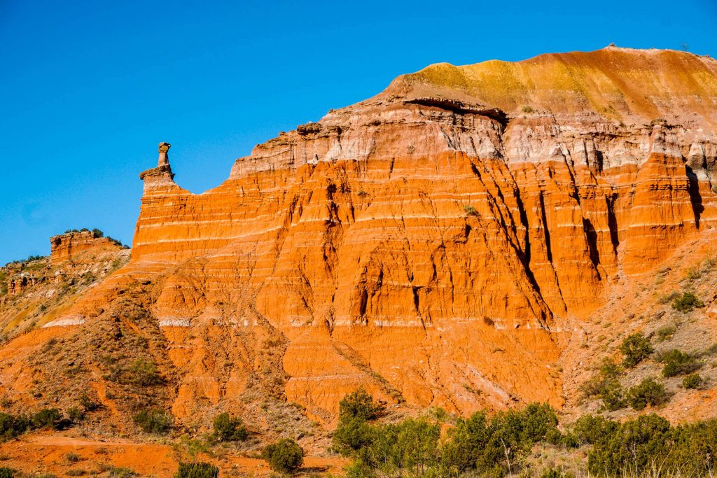 A beautiful rock formation with layers of orange, yellow and white at Palo Duro Canyon State Park.