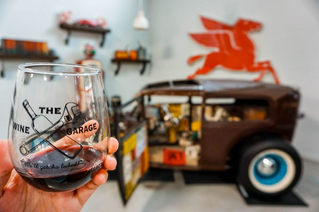 A stemless glass of red wine with a Rat Rod classic car in the background at The Wine Garage in Fredericksburg, Texas.