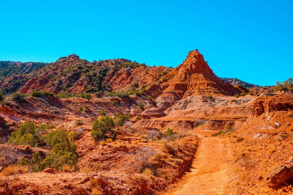 A red dirt hiking trail with red rock formations at Caprock Canyons State Park.