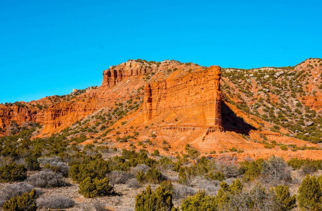 A beautiful overlook of a towering red rock formation with canyons behind it at at Upper South Prong - one of the best things to do in Caprock Canyons State Park.