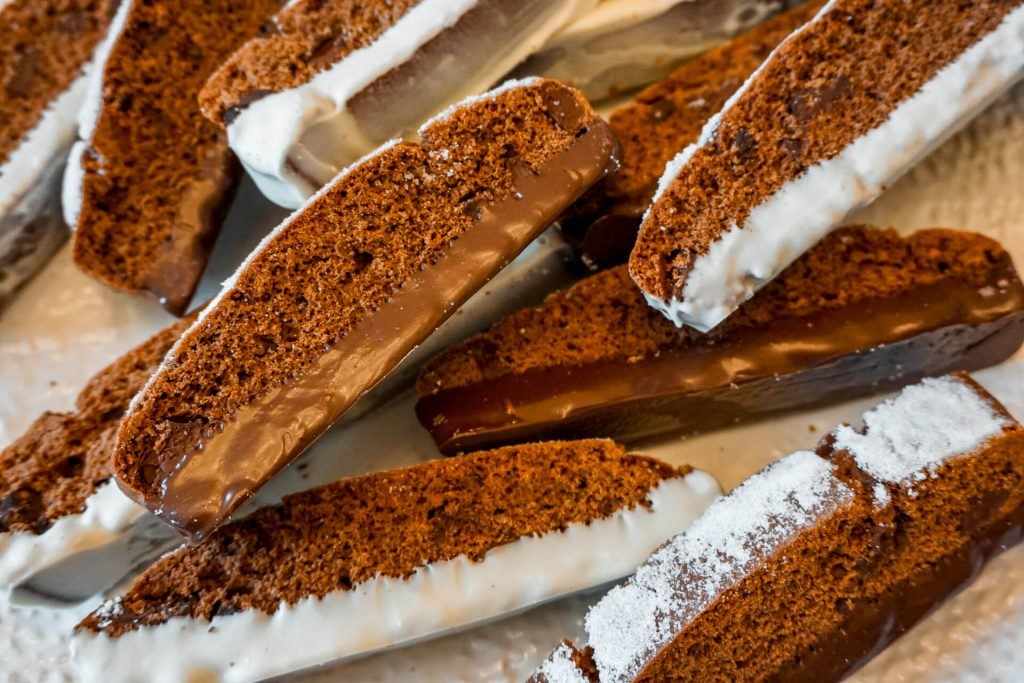 Triple Chocolate Biscotti dipped in dark and white chocolate laying sideways.