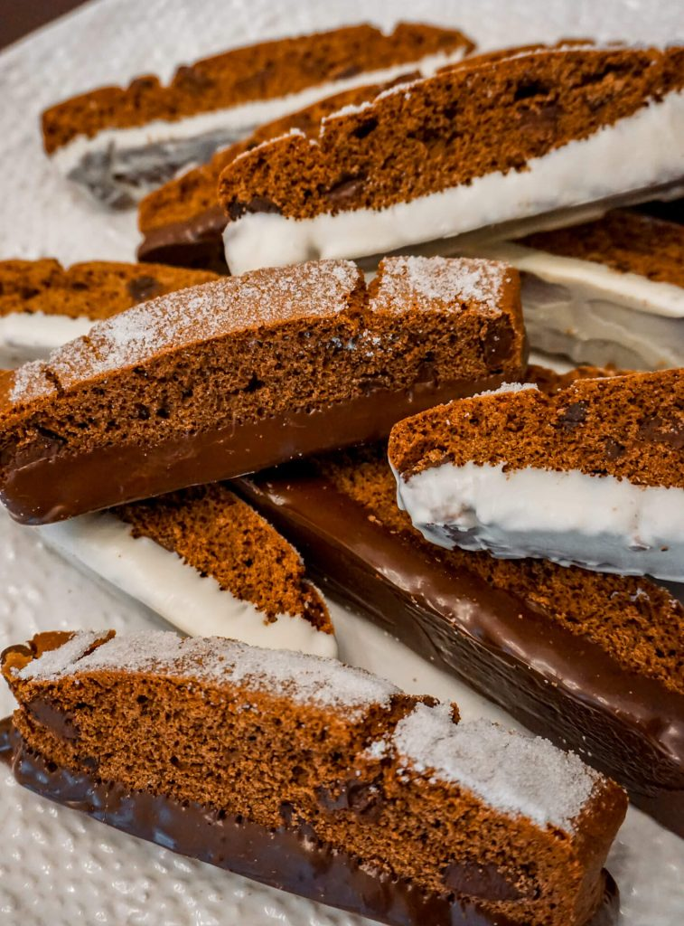 Triple Chocolate Biscotti dipped in dark and white chocolate with sugar sprinkled on top.