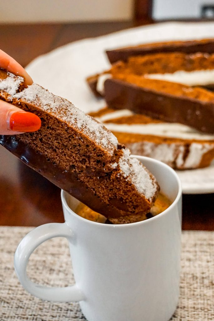 A hand dunking a Triple Chocolate Biscotti in a cup of hot coffee.