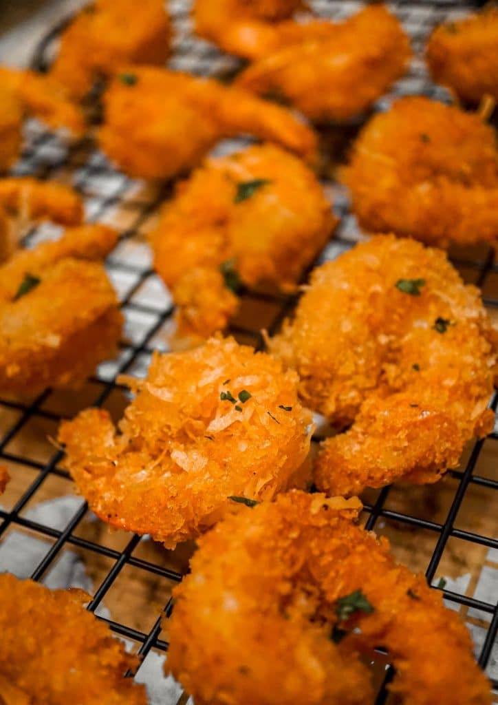 Coconut shrimp laying on a cooling rack.