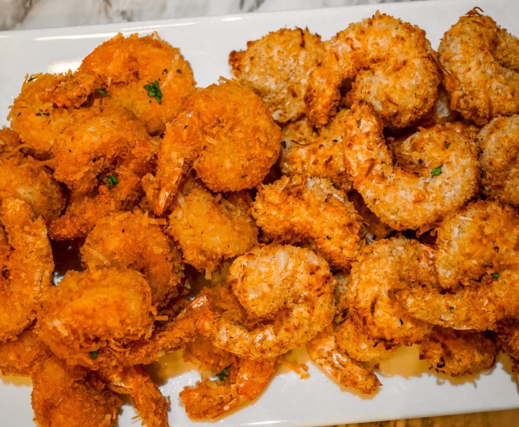 A plate of two different fried coconut shrimp. On the left is coconut shrimp fried in oil. On the right is coconut shrimp fried in an air fryer.