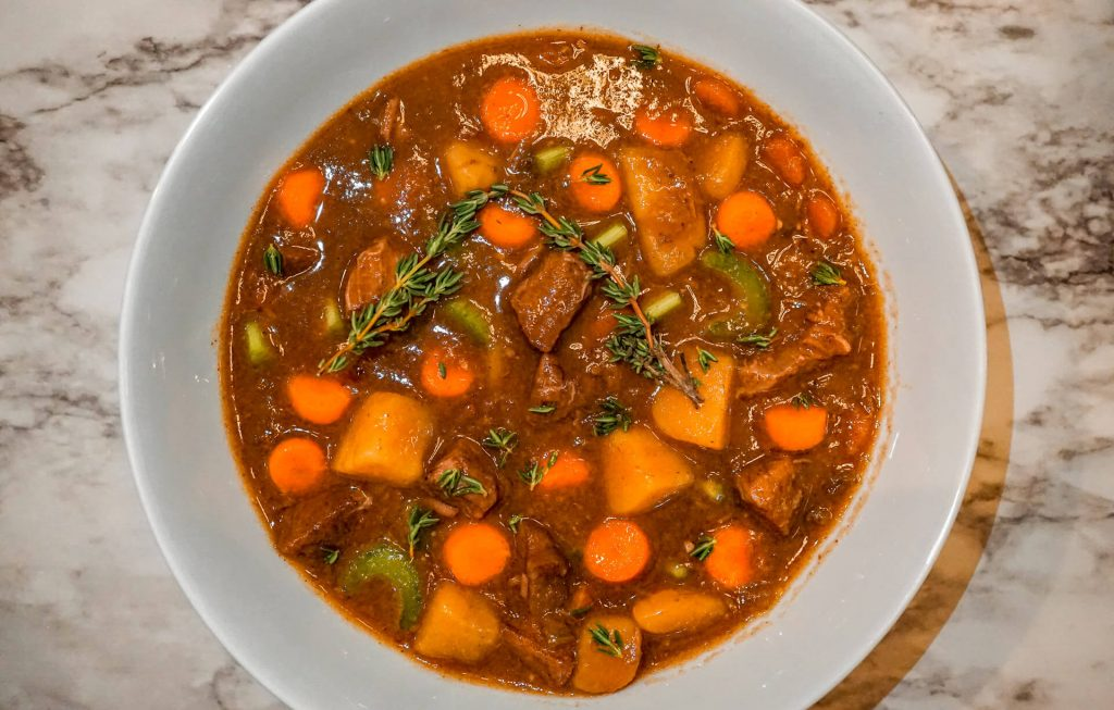 A bowl of Instant Pot Guinness Beef Stew - sprigs of fresh thyme, cubes potatoes, carrots, celery, and chuck roast in a beef broth.