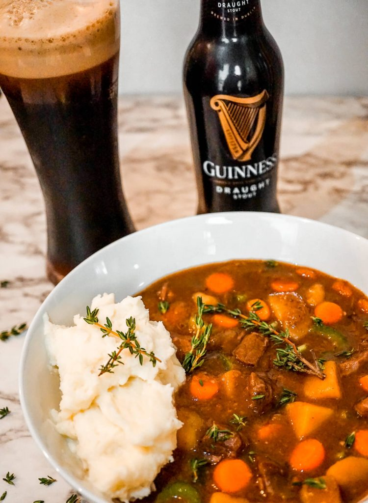 A glass and bottle of Guinness behind a bowl of Instant Pot Guinness Beef Stew with mashed potatoes.