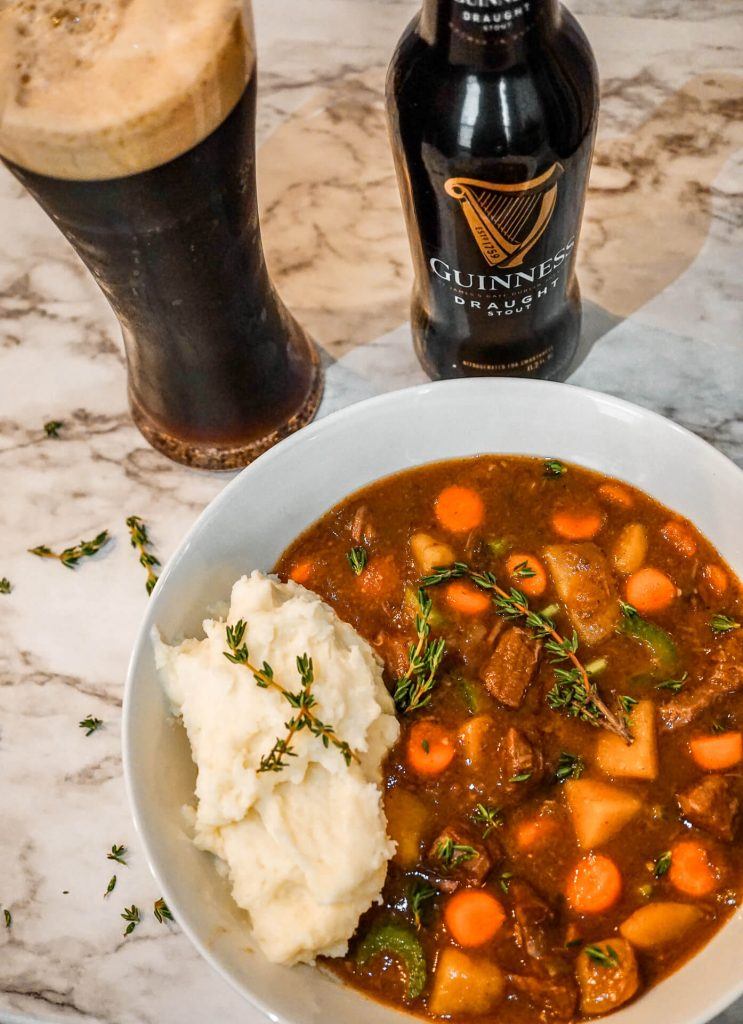 A glass of Guinness alongside a bottle of Guinness and a bowl of Instant Pot Guinness Beef Stew with mashed potatoes.