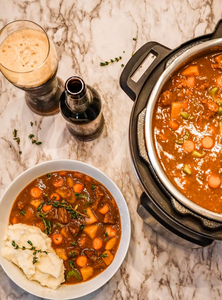 Birdseye view of a glass and bottle of Guinness alongside an Instant Pot and bowl full of Guinness Beef Stew.